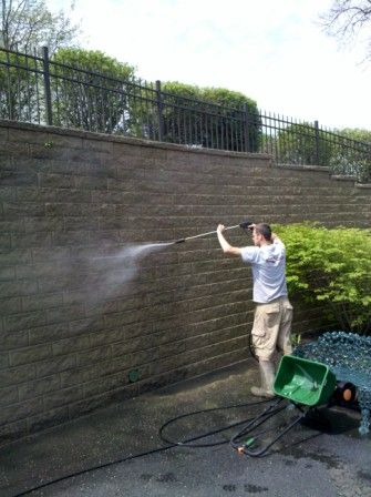 Paver Protector power washing a moldy retaining wall