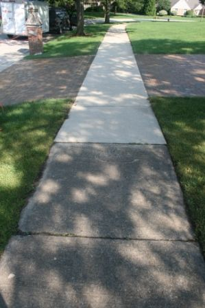 dirty concrete sidewalk cleaned by Paver Protector